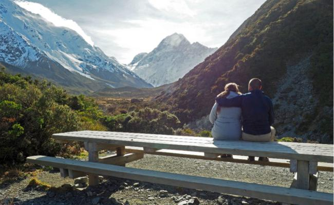 couple sit at rest stop on hooker valley hike in winter