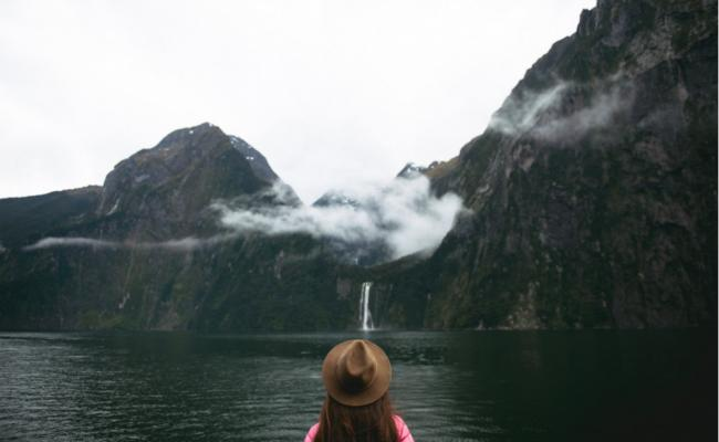 girl in hat looks at waterfall in milford sound