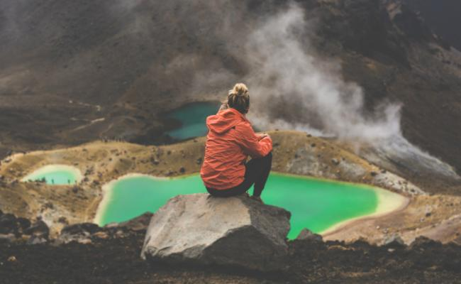 girl sits in front of emerald lakes on tongariro crossing day hike