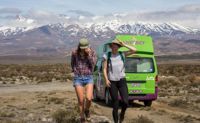 two girls walking in front of jucy camper