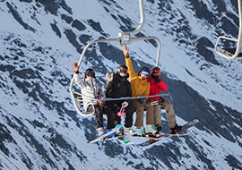 friends on a skilift at treble cone ski field