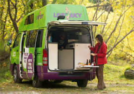 girl cooking in back of jucy campervan in new zealand