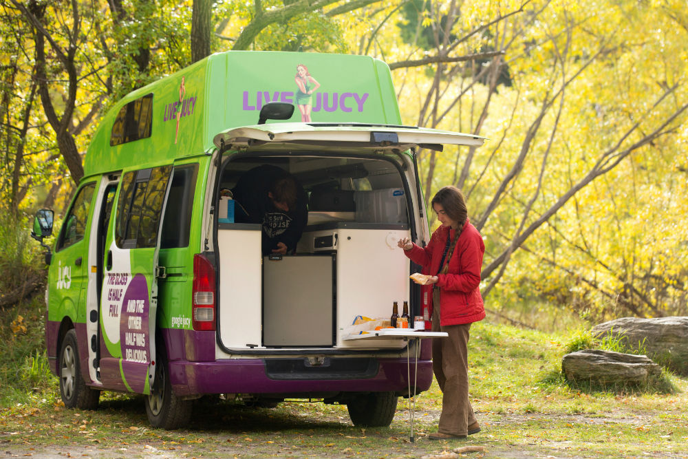 girl cooking in back of jucy campervan