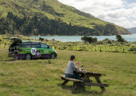 girl has picnic while freedom camping in new zealand