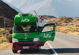 girl holds arms out of jucy campervan