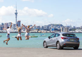 three friends jumping in front of view of skytower next to jucy car