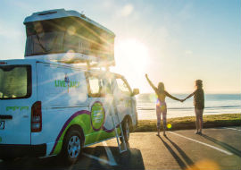 two girls watch sunrise next to a jucy compass camper in auckland