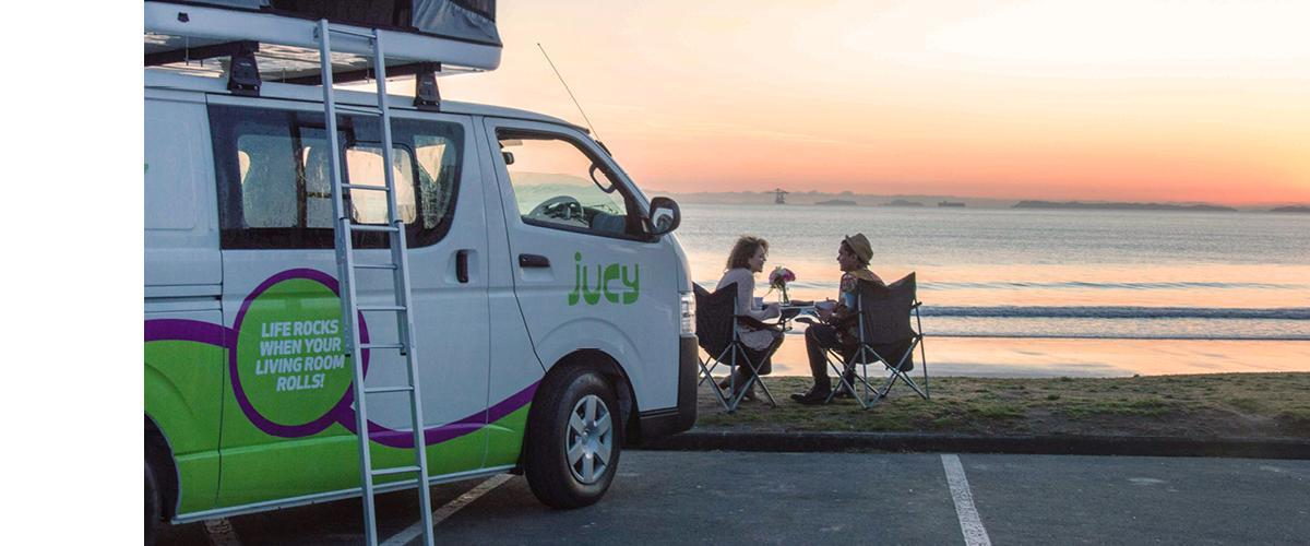 couple having dinner by campervan at sunset